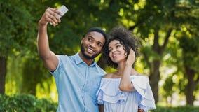 Pares bonitos alegres que fazem o selfie no smartphone fora fotografia de stock