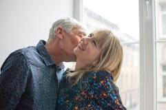 Pares bonitos com a diferen?a da idade que beija perto da janela aberta dentro da casa durante o tempo de mola imagens de stock