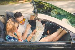 Pares bonitos com o mapa no carro do cabriolet fotos de stock