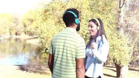 Pares bonitos com os fones de ouvido que escutam a música e que dançam pelo lago vídeos de arquivo