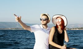 Pares bonitos de amantes que navegam em um barco Dois modelos de forma que levantam em um barco de navigação no por do sol Imagens de Stock
