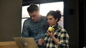 Pares bonitos de dois povos atrativos novos que usam o portátil Concentração cheia Tempo da despesa junto filme