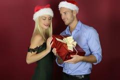 Pares bonitos do Natal que guardam o presente foto de stock royalty free