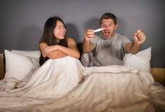 Pares bonitos e felizes novos junto na cama que olha o resultado positivo no teste de gravidez com sur grávido da esposa ou da am foto de stock royalty free