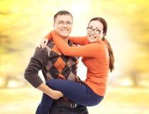 Pares bonitos e felizes que andam e que abraçam no parque do outono Imagem de Stock Royalty Free