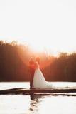 Pares bonitos elegantes do casamento que levantam perto de um lago no por do sol fotos de stock