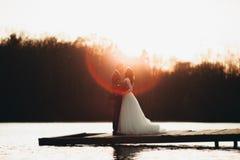 Pares bonitos elegantes do casamento que levantam perto de um lago no por do sol imagens de stock