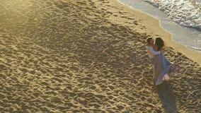 Pares bonitos em uma praia que aprecia seus sentimentos O homem considerável roda em sua menina bonita das mãos no vestido leve l vídeos de arquivo