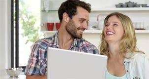Pares bonitos eretos que olham seu portátil video estoque