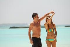 Pares bonitos felizes que apreciam na praia no dia ensolarado h de Maldivas fotografia de stock royalty free