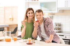 Pares bonitos felizes que comem o café da manhã com pão saboroso na tabela na cozinha Fotografia de Stock Royalty Free