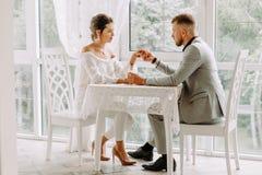 Pares bonitos felizes que sentam-se em um restaurante e em uma fala Imagem de Stock Royalty Free