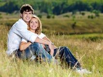 Pares bonitos felizes que sentam-se no prado Imagem de Stock