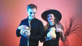 Pares bonitos, homem e mulher em trajes da bruxa e zombi o Dia das Bruxas, 4k, tiro do lento-movimento, abóbora da posse e crânio video estoque