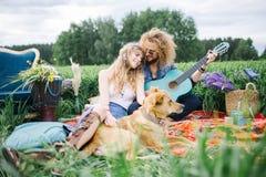 Pares bonitos jovenes del hippie con la guitarra y el perro al aire libre imagen de archivo