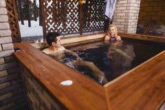 Pares bonitos na banheira de hidromassagem no inverno fotos de stock royalty free