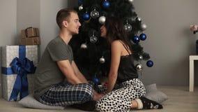 Pares bonitos no amor que senta-se no assoalho da sala de visitas ao lado de uma árvore de Natal e de umas caixas decoradas Vista vídeos de arquivo