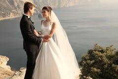 Pares bonitos noiva lindo no vestido de casamento que levanta com o noivo elegante no custo do mar Imagem de Stock Royalty Free