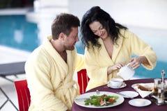 Pares bonitos nos roupões que comem o café da manhã junto no hotel Foto de Stock