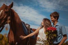 Pares bonitos novos com um cavalo filtrado Foco seletivo Imagens de Stock
