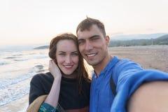 Pares bonitos novos de Selfie na praia imagens de stock