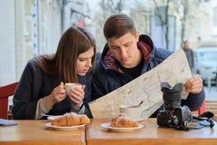 Pares bonitos novos de turistas que descansam no caf? exterior, lendo o mapa da cidade, caf? bebendo com croissant foto de stock royalty free