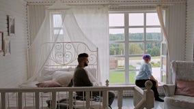 Pares bonitos novos em camisetas mornas em uma casa de campo contra a janela Abra?os e relacionamentos de fam?lia filme