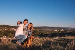 Pares bonitos novos felizes que fazem o selfie fora fotos de stock