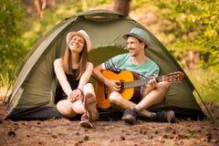Pares bonitos novos felizes que sentam-se com a guitarra na floresta na barraca o homem feliz confessa o amor imagens de stock