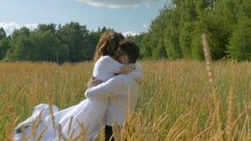 Pares bonitos novos na roupa branca que abraça dentro em um campo de trigo filme