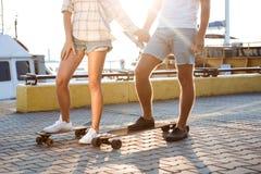 Pares bonitos novos que andam no beira-mar, skateboarding Feche acima dos pés fotografia de stock