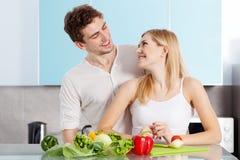 Pares bonitos novos que cozinham em casa Fotografia de Stock