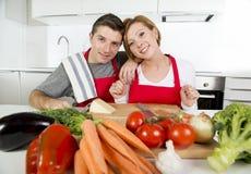 Pares bonitos novos que trabalham em casa a cozinha que prepara o sorriso vegetal da salada junto feliz Fotos de Stock Royalty Free