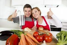 Pares bonitos novos que trabalham em casa a cozinha que prepara o sorriso vegetal da salada junto feliz Foto de Stock Royalty Free