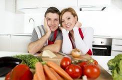 Pares bonitos novos que trabalham em casa a cozinha que prepara o sorriso vegetal da salada junto feliz Fotografia de Stock Royalty Free