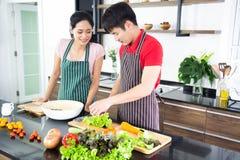Pares bonitos novos românticos que cozinham o alimento na cozinha fotos de stock