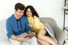 Pares bonitos novos - um menino e uma menina gastam seu lazer junto O par consulta a informação na tabuleta, pegara-a e fotos de stock