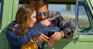 Pares bonitos que discutem no telefone celular em um dia ensolarado 4k vídeos de arquivo