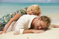 Pares bonitos que encontram-se na areia e que jogam na ilha das Caraíbas, flo Foto de Stock Royalty Free