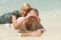 Pares bonitos que encontram-se na areia e que jogam na ilha das Caraíbas, flo Fotografia de Stock