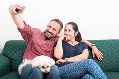 Pares bonitos que fazem o selfie com seu cão imagem de stock royalty free