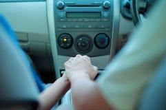 Pares bonitos que guardam as mãos de se no carro fotos de stock royalty free
