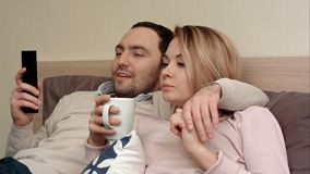 Pares bonitos que olham um filme em casa, o chá bebendo da mulher e falando a um sócio Fotografia de Stock Royalty Free