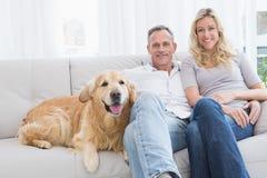 Pares bonitos que relaxam junto no sofá com seu cão Imagens de Stock Royalty Free