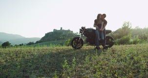 Pares bonitos que sentam-se na motocicleta parada a apreciar a ideia da paisagem da natureza, eles que abraçam-se e vídeos de arquivo