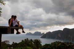 Pares bonitos que sentam-se na plataforma de madeira com opiniões da ilha de Phi Phi e o céu nebuloso imagem de stock