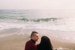 Pares bonitos que sentam-se na praia, abraçando e olhando lovingly se Fundo do seascape do inverno encarregado Fotografia de Stock Royalty Free