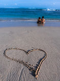 Pares bonitos que sentam-se na praia e que enjoing o mar Imagens de Stock