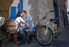 Pares bonitos que sentam-se no café do passeio perto de sua bicicleta em tandem Imagens de Stock