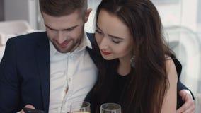 Pares bonitos que sentam-se no restaurante que olha o smartphone em um dia ensolarado fotografia de stock royalty free